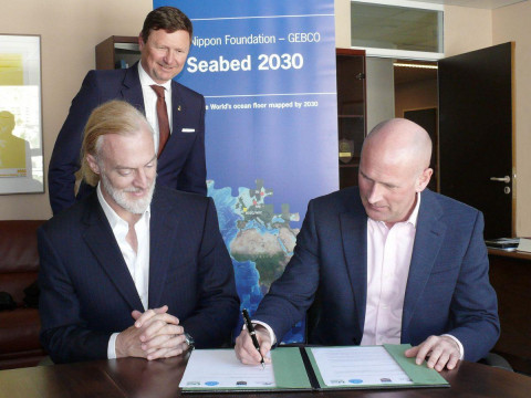 Victor Vescovo (left) and Dr Graham Allen (right) sign the Memorandum of Understanding in the presence of Dr Mathias Jonas, Secretary General of the International Hydrographic Organization